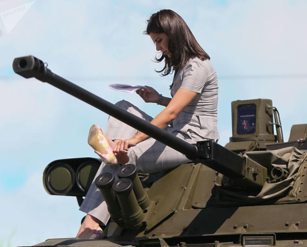 Garota sentada em um tanque em uma das exposições na região de Moscou, julho de 2010
