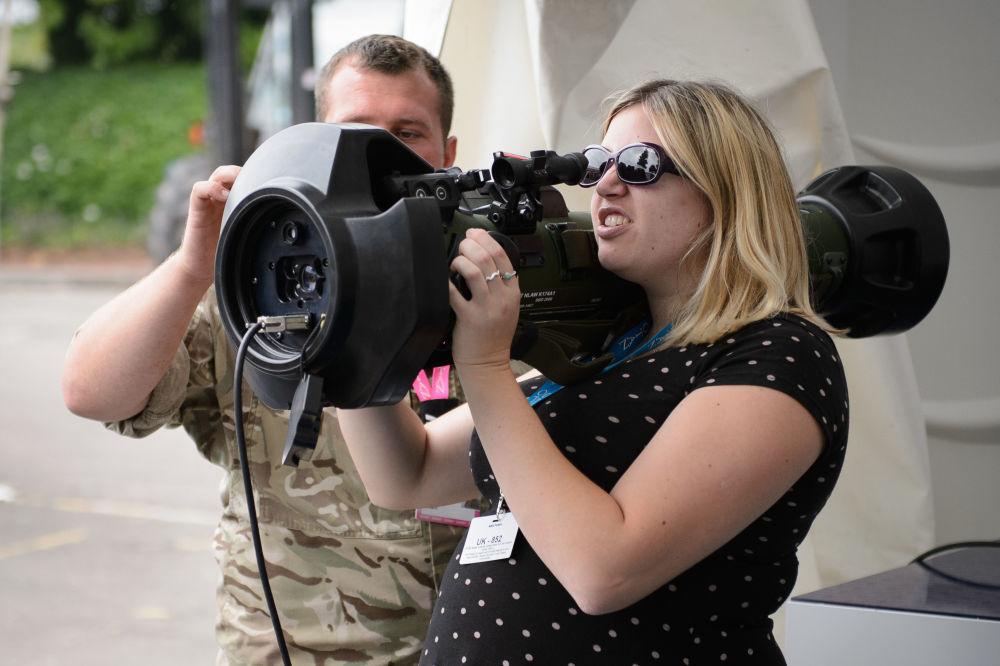 Mulher testa armas na exposição da cúpula da OTAN, setembro de 2014
