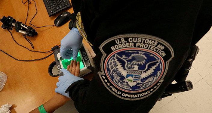 Uma mulher que está buscando asilo tem suas impressões digitais tomadas por um oficial de fronteira dos EUA.