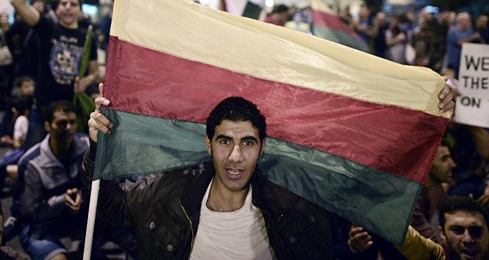 Um homem prende a bandeira do Partido de União Democrática (PYD) dos curdos sírios.