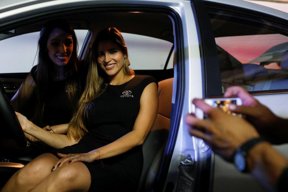 Modelos dentro de um Toyota Corolla durante exposição em Caracas, Venezuela