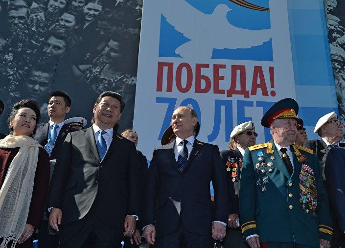 Vladimir Putin (centro) e Xi Jinping (esquerda, com a esposa, Peng Liyuan), durante a Parada da Vitória em Moscou, em 9 de maio de 2015