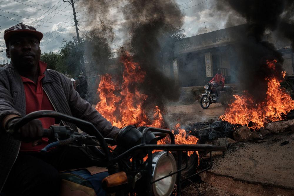 Motociclista passa pelas barricadas em chamas na rua, instaladas pelos apoiantes do candidato do partido NASA (Super Aliança Nacional) nas eleições presidenciais, Raila Odinga, no Quênia