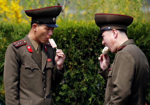 Militares norte-coreanos disfrutam de sorvete em uma das ruas de Pyongyang