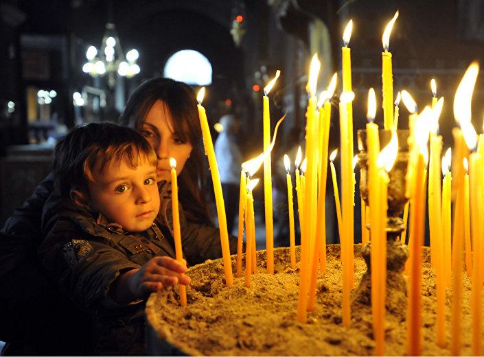 Fiel com seu filho em uma igreja ortodoxa, Salonica, Grécia