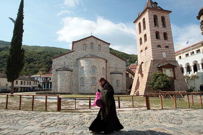 Monge caminhando perto de uma igreja no Monte Atos