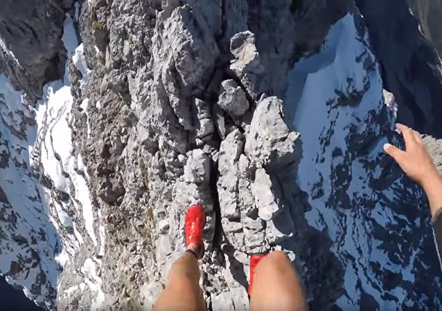 Jovem balança no pico de montanha abrupta nos Alpes