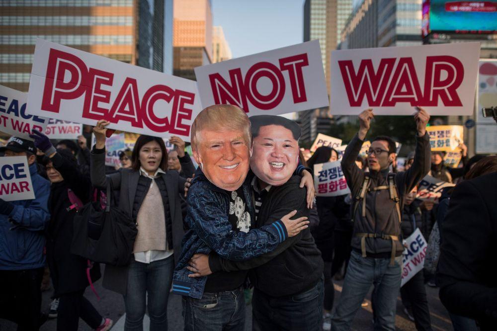 Participantes de manifestação pacifista com máscaras de Trump e Kim Jong-un em Seul