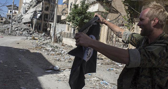 Soldado segurando bandeira do Daesh em Raqqa, Síria