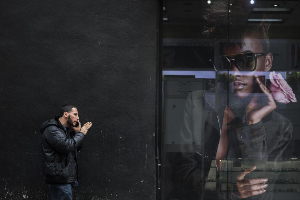 Homem fala de celular perto de cartaz em uma das ruas de Nova York