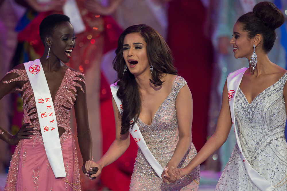 Miss Índia, Manushi Chhilar, reage à sua vitória no concurso Miss Mundo 2017 ao lado da Miss França, Aurore Andrée Raphaelle Kichenin (à direita), e Miss Quênia, Magline Jeruto (à esquerda), na cidade chinesa de Sanya, em 18 de novembro de 2017