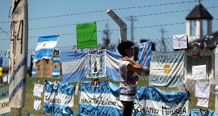 Mulher olhando para mensagens e sinais de apoio aos 44 tripulantes do submarino perdido ARA San Juan