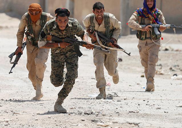 Combatentes curdos correm pelas ruas de Raqqa, Síria (foto de arquivo)