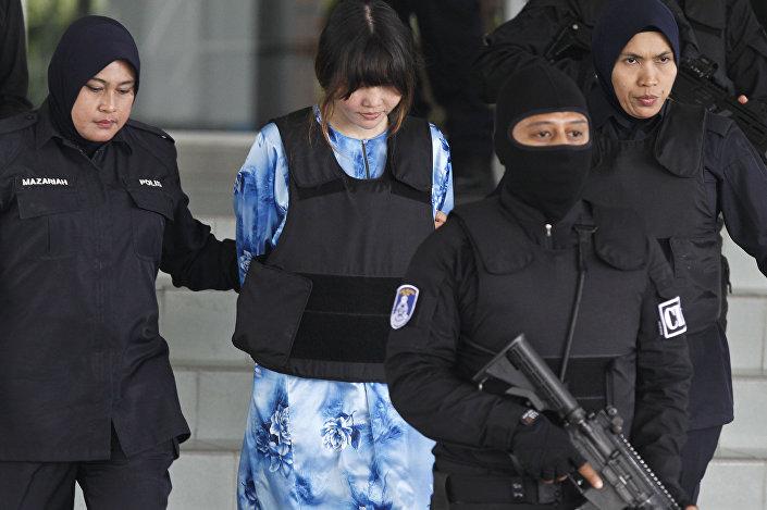 Vietnamita Doan Thi Huong (de vestido e colete à prova de balas) acompanhada por policiais enquanto sai do tribunal em Shah Alam, Malásia