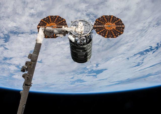 Nave espacial estadunidense Cygnus está sendo acoplado à Estação Espacial Internacional através de um braço robótico pelos astronautas Paolo Nespoli e Randy Bresnik, em 14 de novembro de 2017