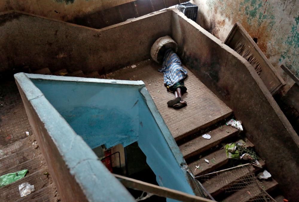 Mendigo dorme em escada em um dos mercados de Bengaluru, Índia