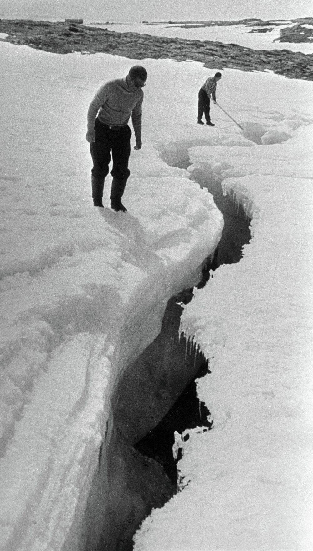 Exploradores polares junto a uma fenda profunda no gelo da Antártida