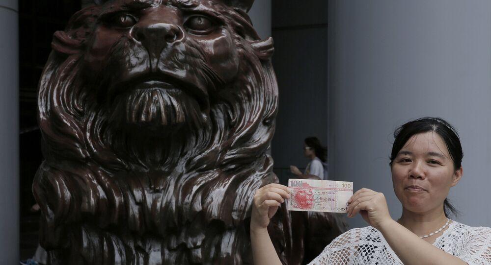 Mulher segura cédula de dólar de Hong Kong diante de estátua de leão, símbolo da cidade