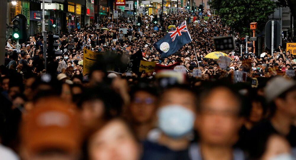 Bandeira colonial de Hong Kong esvoaça em uma marcha de protestos contra a lei antiextradição na estação ferroviária West Kowloon Express Link, em Hong Kong, China, 7 de julho de 2019