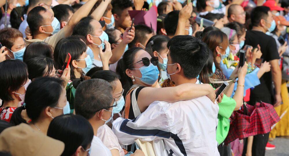 Mulher abraça estudante durante formatura de estudantes em Wuhan, epicentro da COVID-19 na China