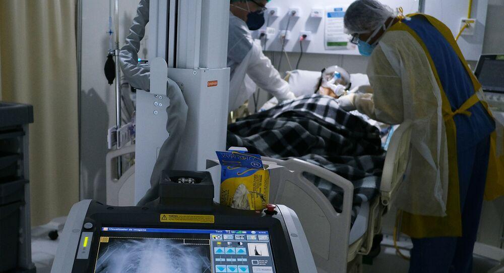Profissionais da saúde examinam um paciente com COVID-19 no Hospital de Campanha Lagoa-Barra, no Rio de Janeiro, Brasil, 2 de julho de 2020