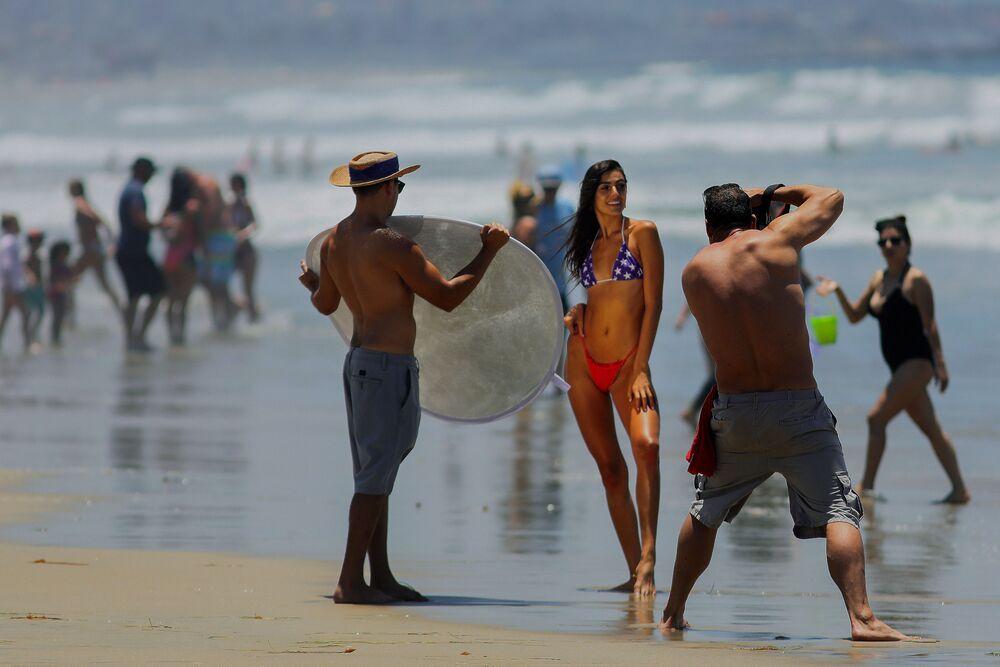 Mulher posa para fotografia em praia de San Diego, nos Estados Unidos