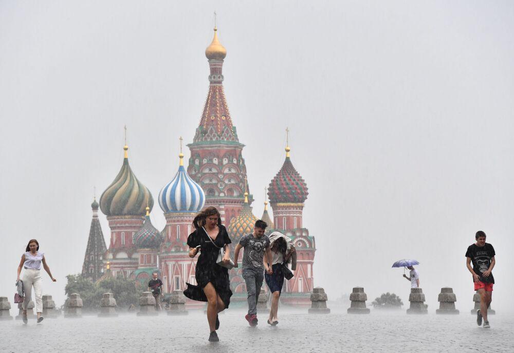 Pessoas caminham pela Praça Vermelha, em Moscou, enquanto chove