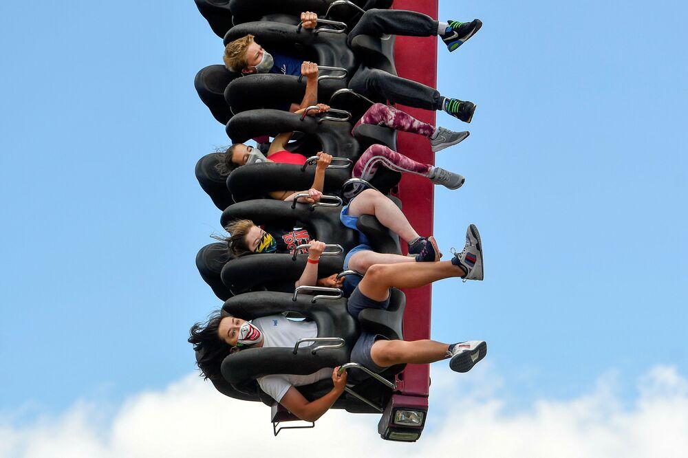 Pessoas com máscaras em parque de diversões no Reino Unido