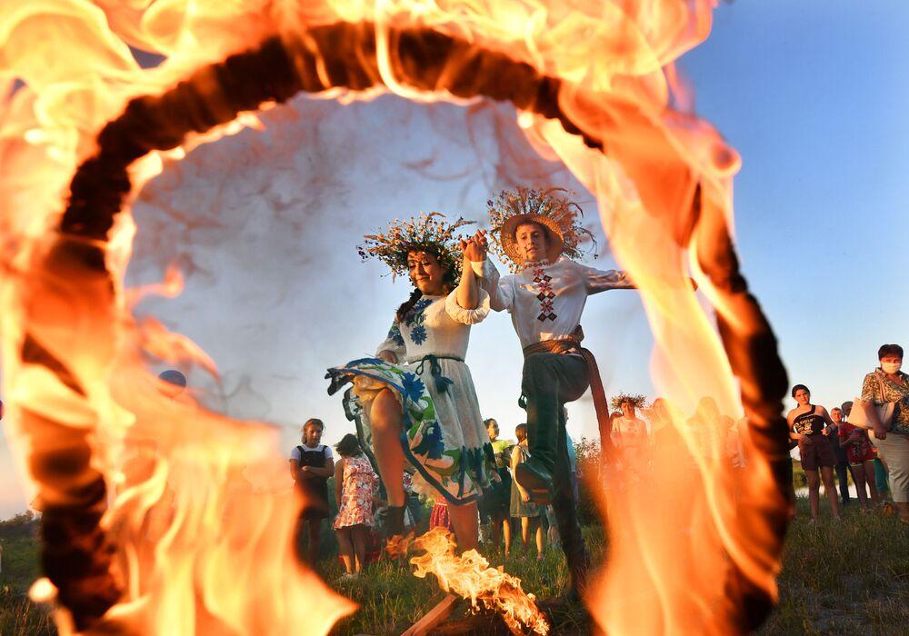 Imagem de jovens saltando sobre anel de fogo na festa tradicional Ivan Kupala, na cidade de Turov, na Bielorrússia