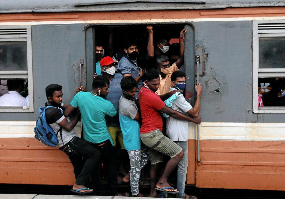Passageiros com máscaras para se protegerem do coronavírus lotam vagão de trem na cidade de Colombo