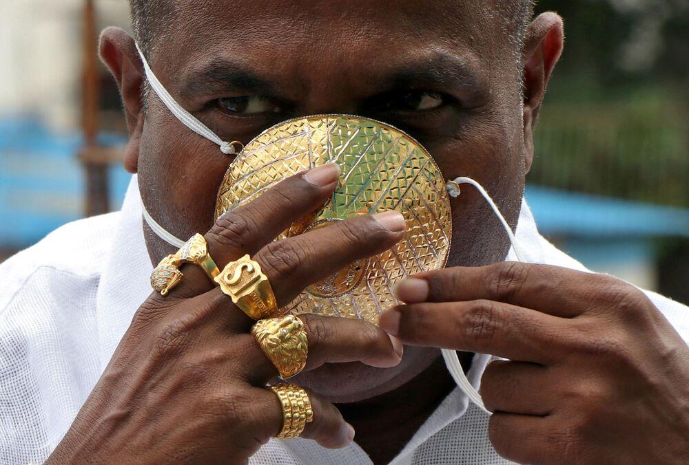 Shankar Kurkhade demonstra sua máscara de ouro na cidade indiana de Pune