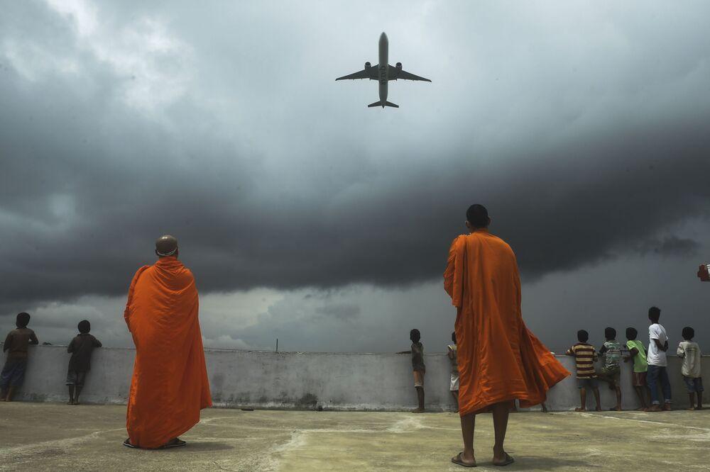 No topo de um edifício budista, monges observam avião decolando do Aeroporto Internacional Netaji Subhash Chandra Bose, enquanto autoridades indianas relaxam medidas adotadas para combater a proliferação do coronavírus