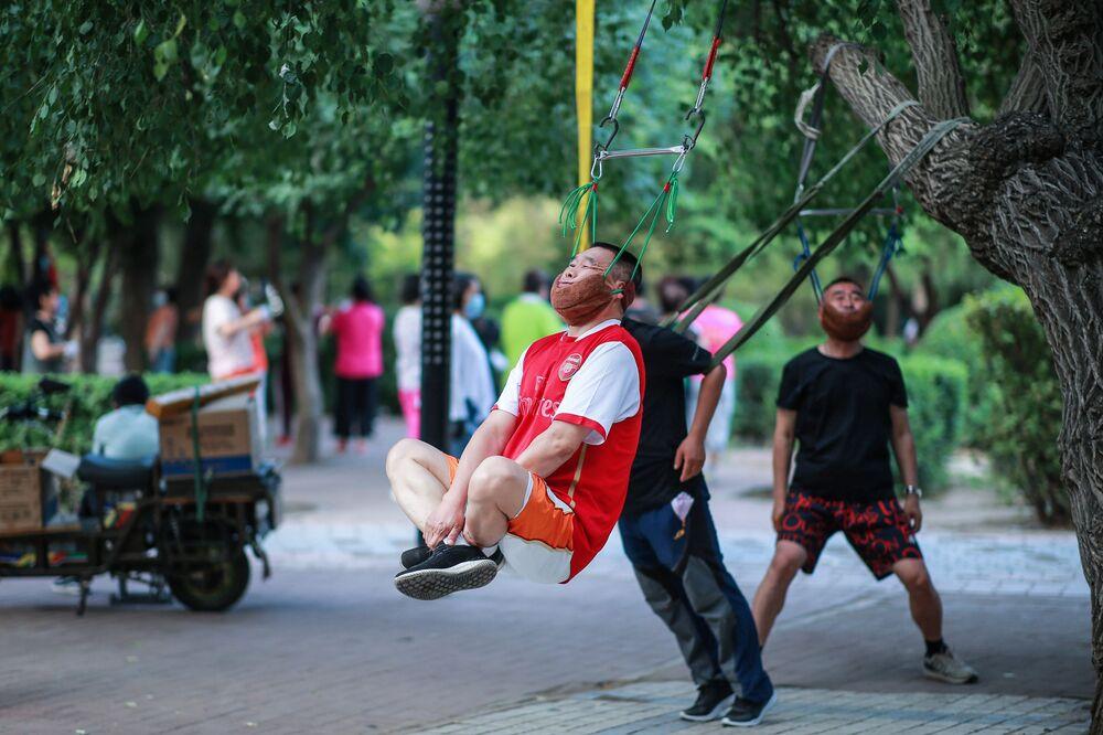 Homens realizam exercícios físicos em parque de Xangai, na China