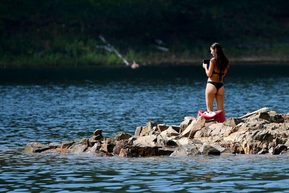 Mulher aproveita dia de sol em baía no mar de Krasnoyarsk