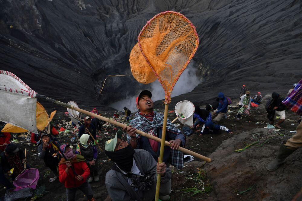 Moradores locais levam redes para tentar capturar moedas jogadas como oferendas em cerimônia religiosa, na Indonésia
