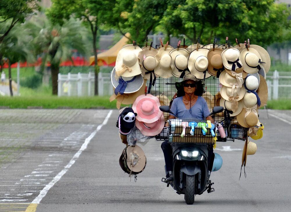 Comerciante passa de moto com diversos chapéus à venda