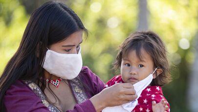 Mulher da etnia guarani coloca máscara em sua filha enquanto aguardam testes da COVID-19 no Instituto Butantan