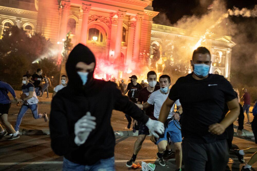 Em Belgrado, manifestantes correm durante manifestação contra medidas de restrição social de combate à COVID-19, em frente ao parlamento sérvio, em 10 de julho de 2020.