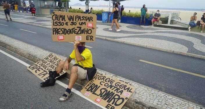 Manifestante exibe cartaz durante protesto contra o presidente Jair Bolsonaro em Copacabana, no Rio de Janeiro