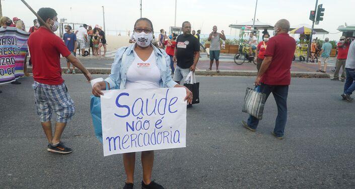 Ativista exibe cartaz em protesto contra a condução da crise da COVID-19 pelo governo brasileiro