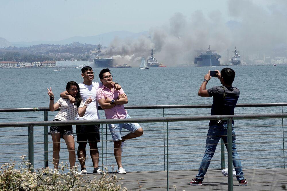 Pessoas tiram fotos próximas a incêndio do navio de assalto anfíbio USS Bonhomme Richard, no estado norte-americano da Califórnia