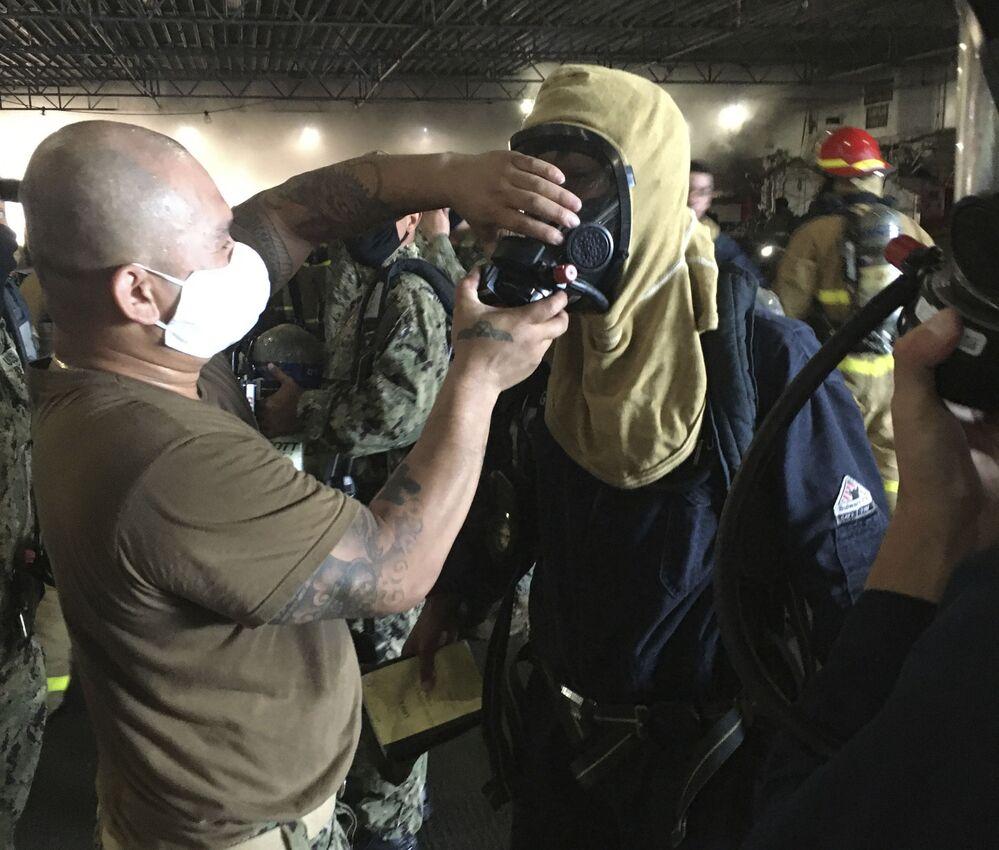 Marinheiros vestem trajes de proteção para combater incêndio no navio de assalto anfíbio USS Bonhomme Richard da Marinha dos EUA
