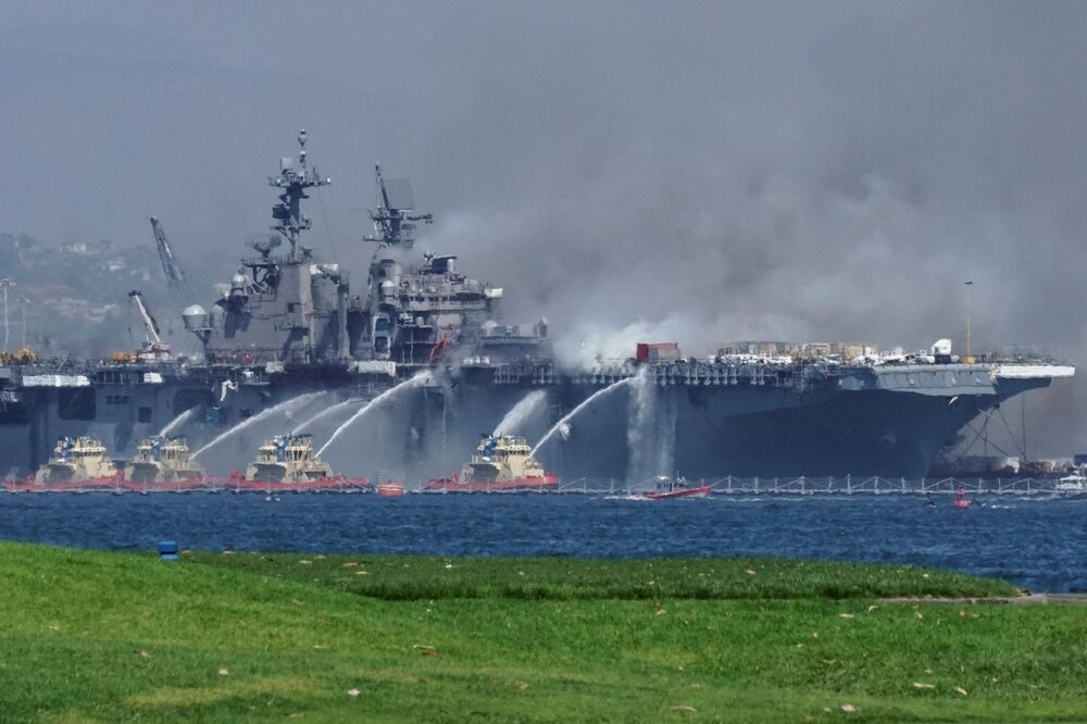 Embarcações direcionam jatos de água ao navio de assalto anfíbio USS Bonhomme Richard para conter um incêndio iniciado neste domingo (12)