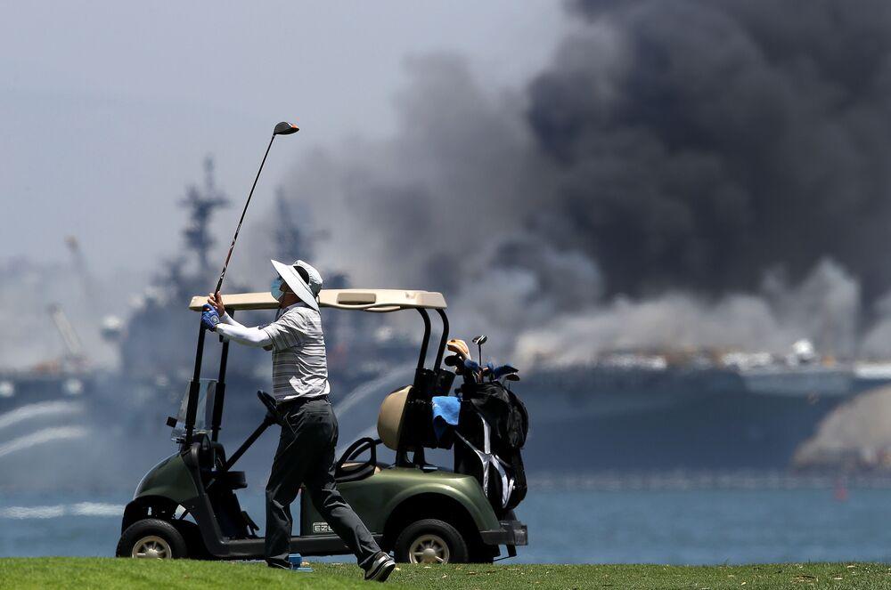 Homem passeia em campo de golfe enquanto navio anfíbio USS Bonhomme Richard enfrenta incêndio em base da Marinha dos EUA