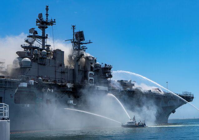 Embarcações no porto de San Diego, nos Estados Unidos, jogam fatos de água no navio de assalto anfíbio USS Bonhomme Richard para deter um incêndio iniciado em 12 de julho