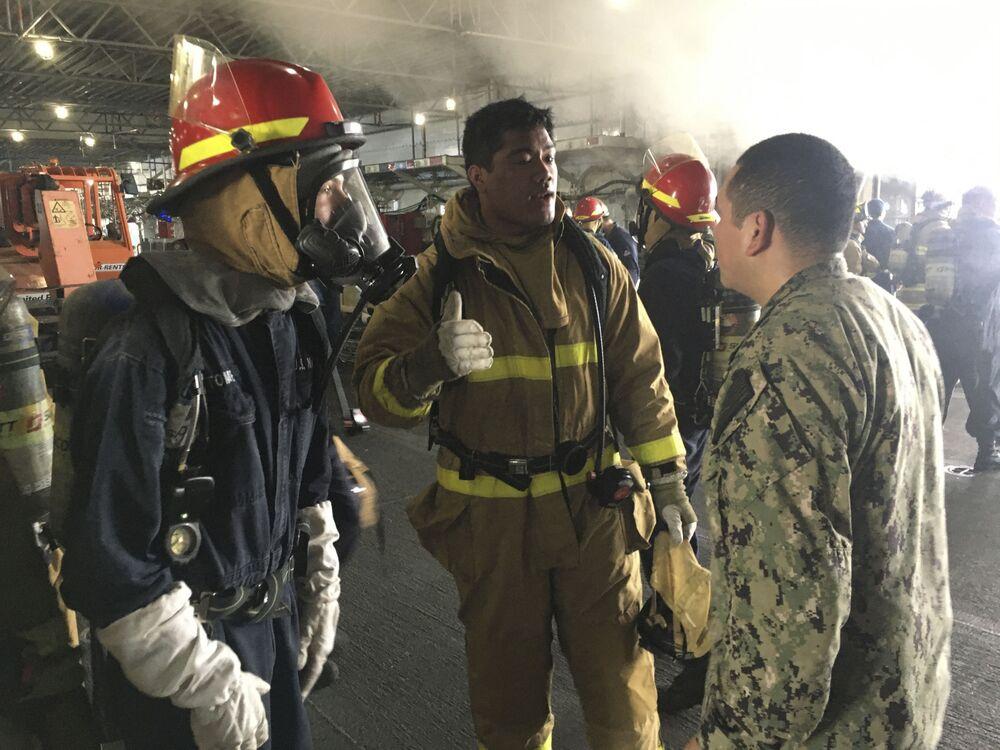 Marinheiros discutem operação para conter a proliferação do fogo durante incêndio no navio de assalto anfíbio USS Bonhomme Richard da Marinha dos EUA