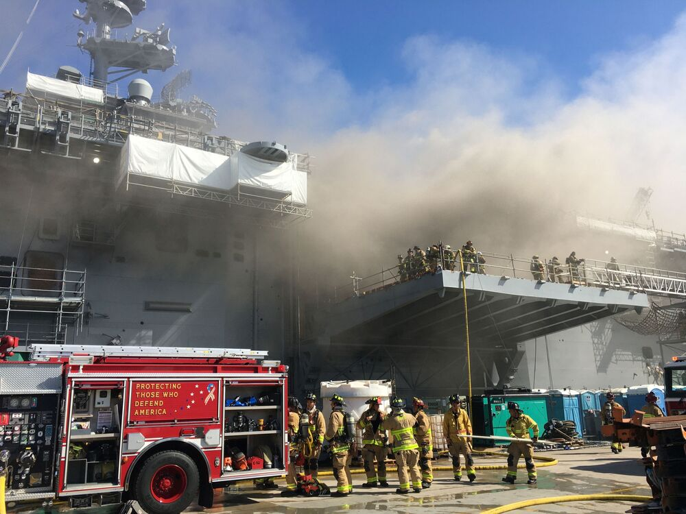 Marinheiros e bombeiros de San Diego, nos Estados Unidos, combatem fogo causado por explosão no navio de assalto anfíbio USS Bonhomme Richard da Marinha dos EUA