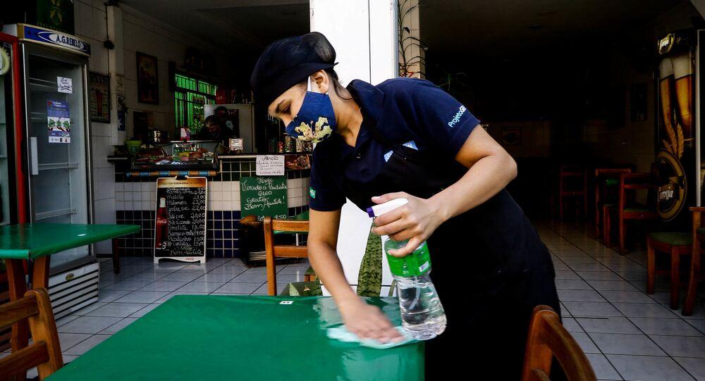 Funcionária limpa mesa em estabelecimento em São Paulo, reaberto em meio à pandemia da COVID-19