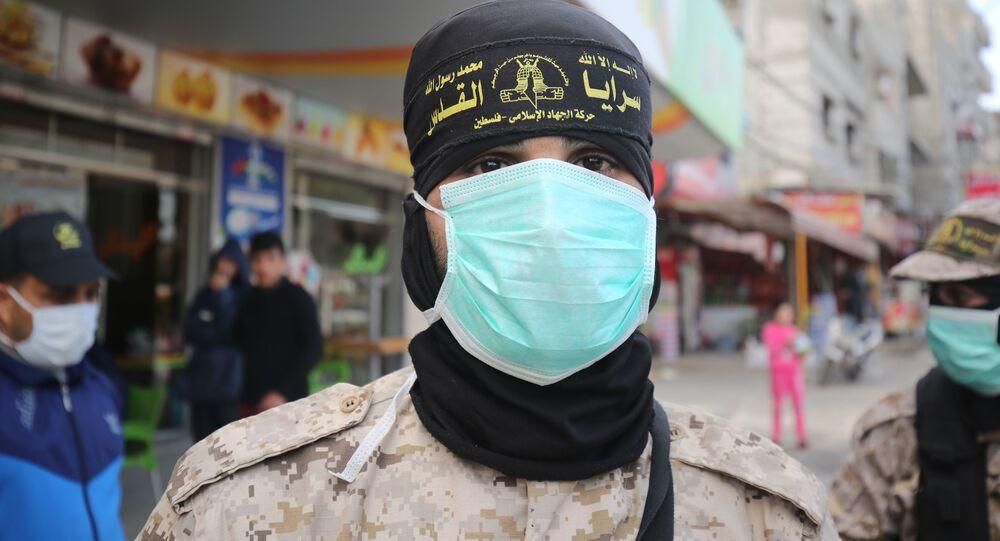 Membro do grupo palestino Jihad Islâmica usa máscara protetora nas ruas de Rafah, na Faixa de Gaza, 26 de março de 2020