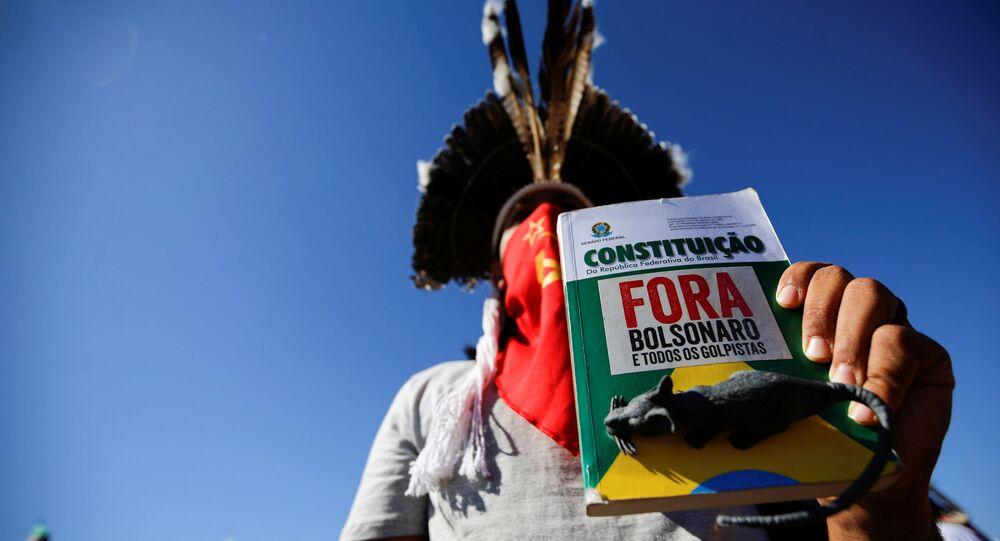Manifestante segura um livro da Constituição Federal com os dizeres Fora Bolsonaro em ato em Brasília
